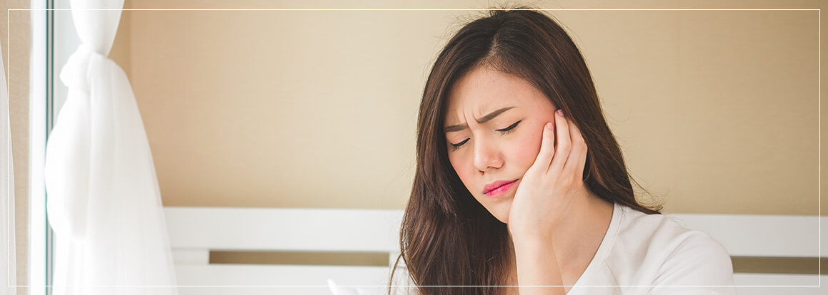 woman holding her jaw, experiencing jaw pain