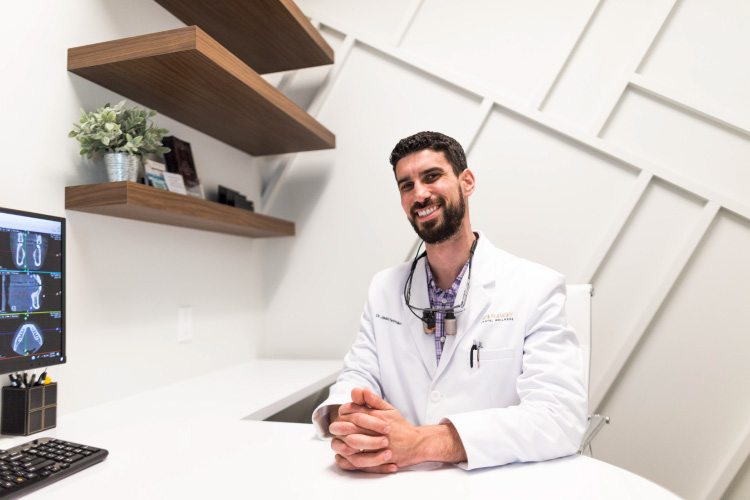 Dr. Perlman wears a white coat and smiles at their office, where he offers mercury-free dentistry