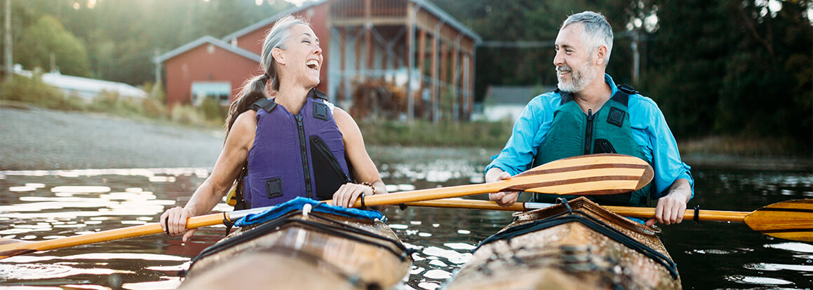 man and woman in kayaks laughing